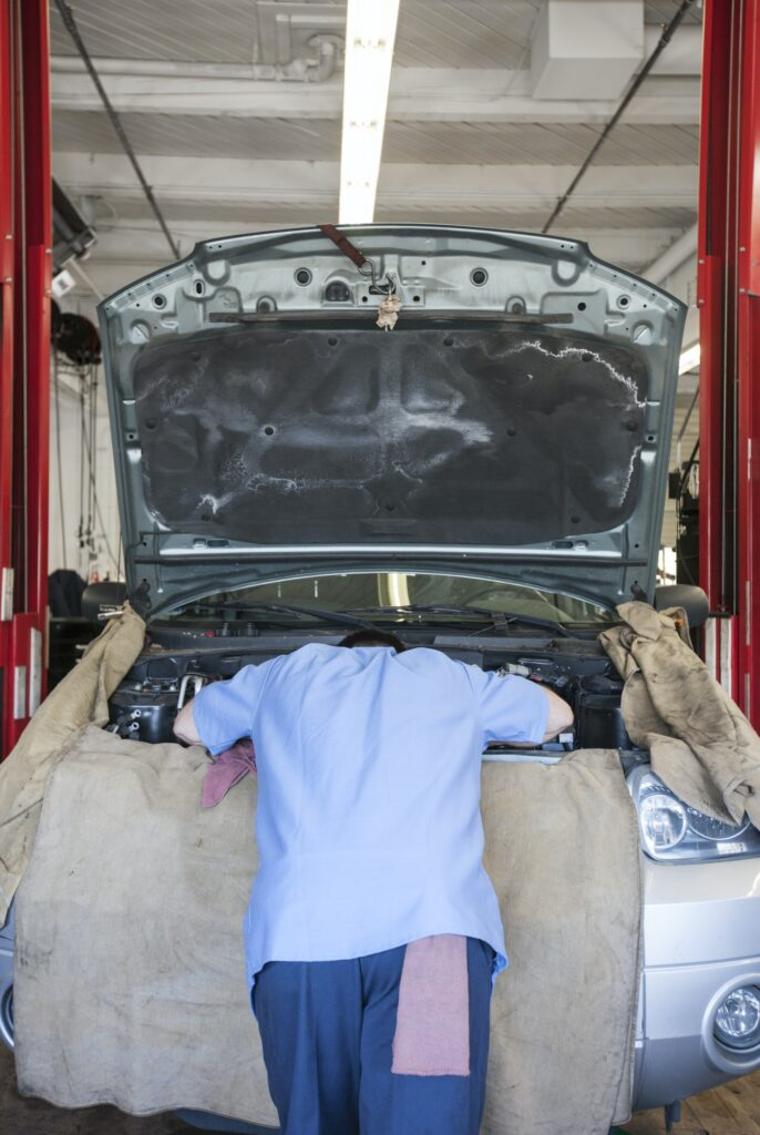 Torso of a mechanic leaning into the engine compartment in an auto repair shop